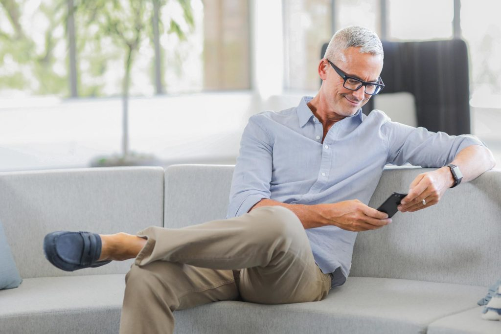 Man sitting on couch while browsing phone